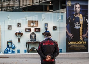 A Deportivo fan checks out the window of the club shop, including the commemorative shirt.