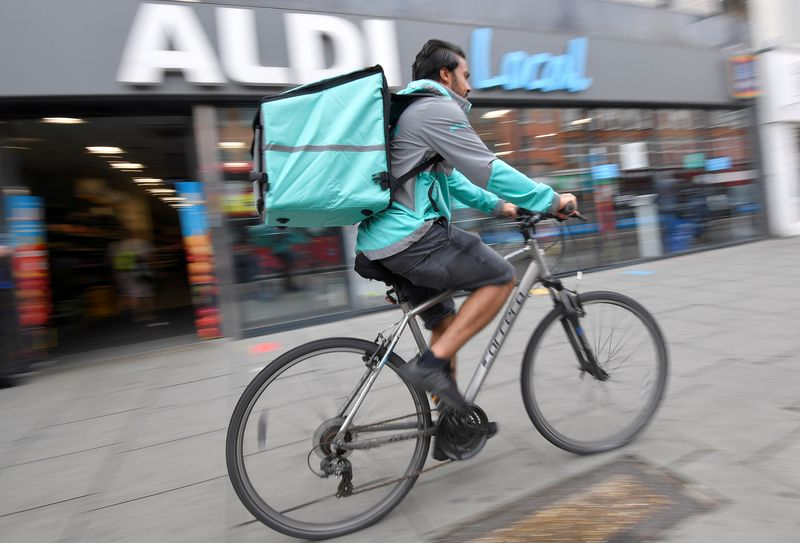 © Reuters. FILE PHOTO: Abdelaziz Abdou, a Deliveroo delivery rider, poses with a bag of Aldi groceries, London