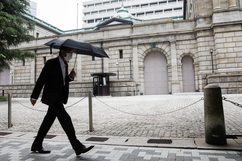 © Reuters. A man wearing a protective mask walks past the headquarters of Bank of Japan amid the coronavirus disease (COVID-19) outbreak in Tokyo