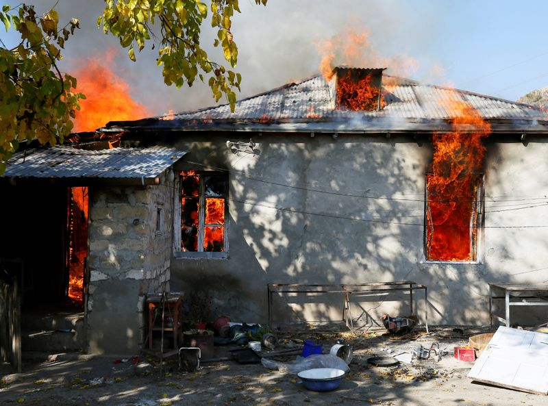 © Reuters. A house is seen set on fire by departing Ethnic Armenians in the village of Cherektar, in the region of Nagorno-Karabakh