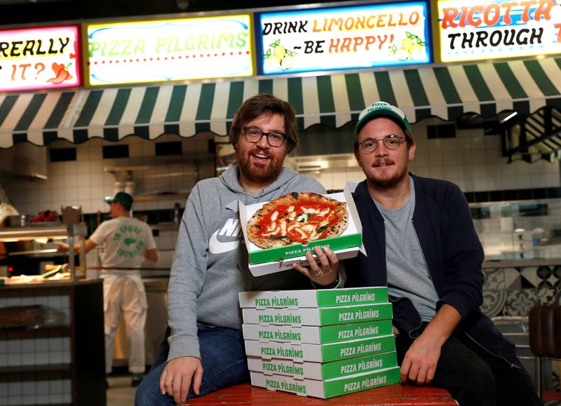 © Reuters. Co-founders of Pizza Pilgrims, brothers Thom (L) and James Elliot, pose for a photograph in one of their restaurants amid the coronavirus disease (COVID-19) outbreak in London