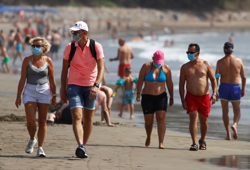 © Reuters. FILE PHOTO: Several people walk along the beach wearing face masks, as the regional government of the Canary Islands forbids smoking without maintaining a safe distance