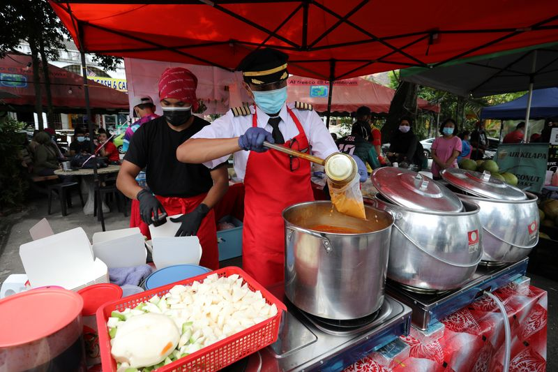 © Reuters. Malaysian former pilot Azrin Mohamad Zawawi prepares food at his food stall in Subang Jaya