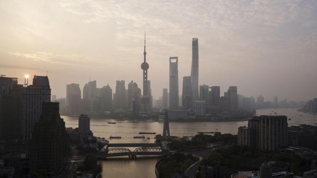 © Bloomberg. The Oriental Pearl Tower, center left, Shanghai World Financial Center, center, and the Shanghai Tower, center right, stand among other buildings in the Lujiazui Financial District along the Pudong riverside in this aerial photograph taken above Shanghai, China, on Monday, April 2, 2018. China's sprawling local government financing system needs