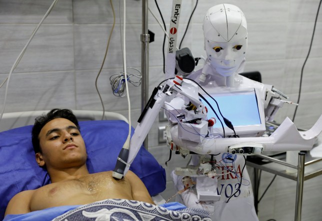 A volunteer is examined by Cira 3, a remote-controlled robot