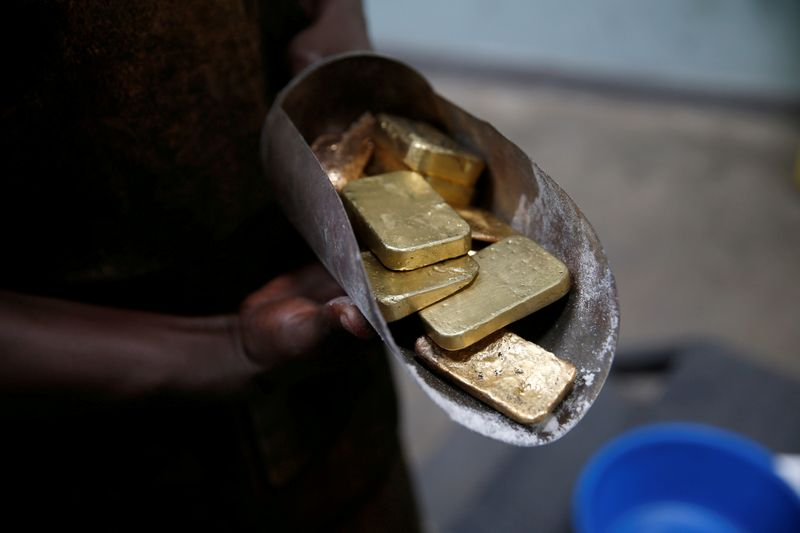 © Reuters. FILE PHOTO: An employee holds gold bars before the refining process at AGR (African Gold Refinery) in Entebbe