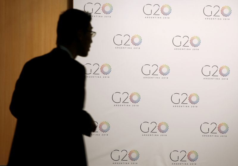 © Reuters. FILE PHOTO: A man stands next to a board with the G20 Meeting of Finance Ministers logo in Buenos Aires