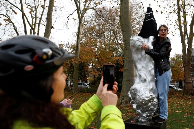© Reuters. A person takes a photo as a protester covers with a t-shirt the Mary Wollstonecraft statue 'Mother of feminism' by artist Maggi Hambling in Newington Green, London