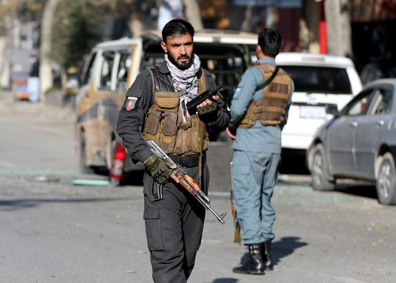 © Reuters. A police officer stands guard after rockets hit residential areas in Kabul