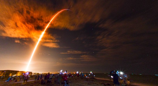 Crowds on the beach in Cape Canaveral, Fla., watch the launch of the SpaceX Falcon 9 Crew Dragon on its Crew-1 mission carrying four astronauts,