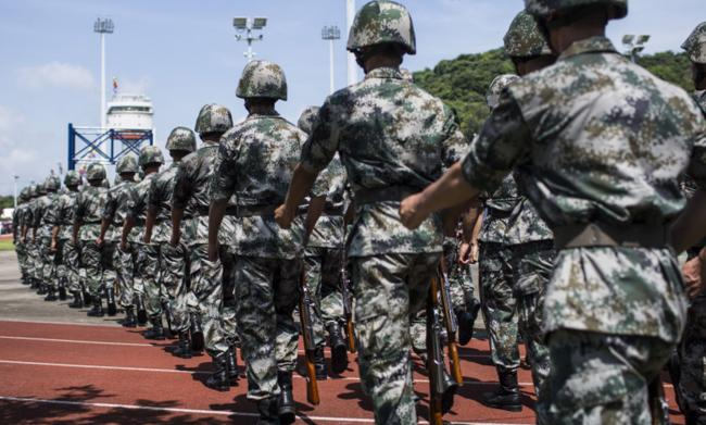 © Bloomberg. Members of the People's Liberation Army march during a demonstration at an open day at the Ngong Suen Chau Barracks in Hong Kong in 2015.