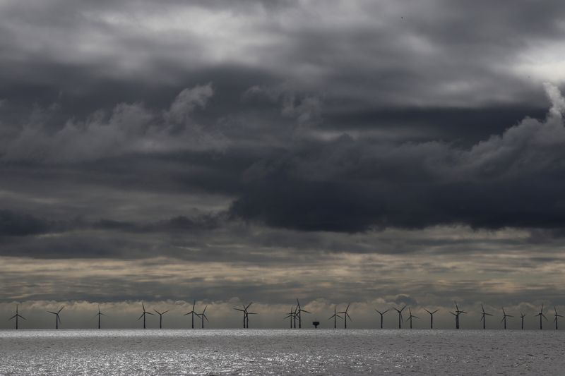 © Reuters. Rain clouds gather over an offshore windfarm off the coast of Finton-on Sea, Britain