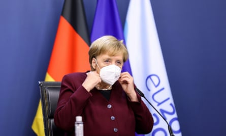 German Chancellor Angela Merkel, seated and wearing a face covering