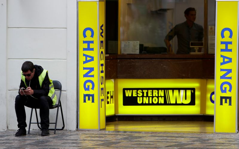 © Reuters. FILE PHOTO: A man sits on a chair next to Western Union currency exchange office in Prague