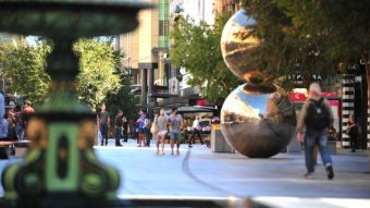 A pedestrian mall with a fountain and a sculpture of two silver balls on top of each other