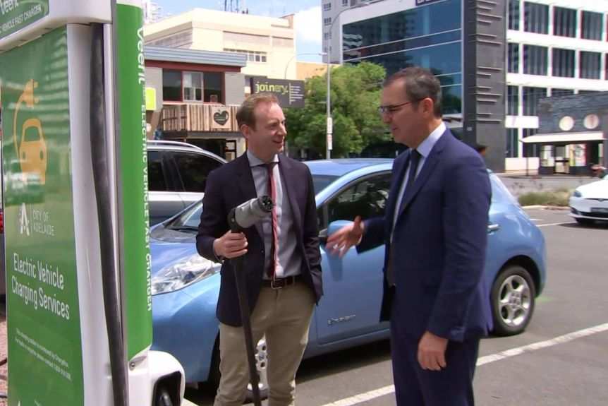 A man holds an electric car plug with another man
