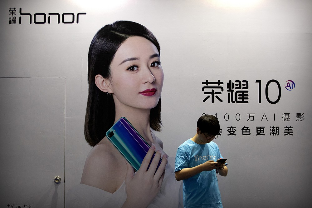 A staff member uses his smartphone in front of a billboard for Chinese smartphone brand Honor at the Global Mobile Internet Conference in Beijing on April 26, 2018. In an announcement Tuesday, Nov. 17, 2020, Chinese tech giant Huawei says it is selling its budget-price Honor smartphone brand in an effort to rescue the struggling business from damaging U.S. sanctions imposed on its parent company. (AP Photo/Mark Schiefelbein)