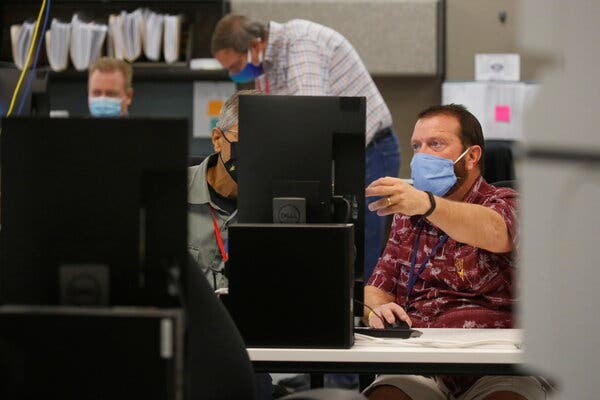 Election workers reviewed ballots in Phoenix on Monday.