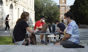 Students sit outside Thompson Library during the first day of fall classes at Ohio State University in Columbus, Ohio, in August 2020.