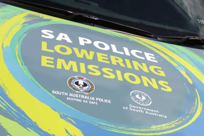 A bonnet of a car with the words SA POLICE LOWERING EMISSIONS on it