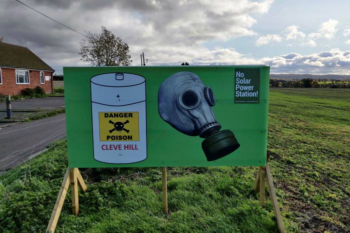 A protest sign stands in the village of Graveney, where hundreds of shipping containers full of battery cells will help deliver power to the UK grid