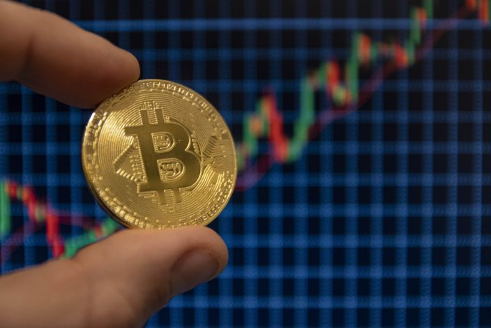 NETHERLANDS - 2020/12/22: In this photo illustration, the Bitcoin golden cryptocurrency commemorative coin seen displayed in front of uptrend graph lines. (Photo Illustration by Nik Oiko/SOPA Images/LightRocket via Getty Images)