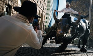 A man sits on the Wall Street bull near the New York stock exchange, which has continued to surge despite the economic crisis.