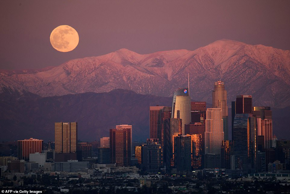The last full moon of 2020, also known as the Cold Moon, rises behind the snow-topped San Gabriel Mountains and the Los Angeles downtown skyline at sunset as seen from the Kenneth Hahn State Recreation Area in Los Angeles