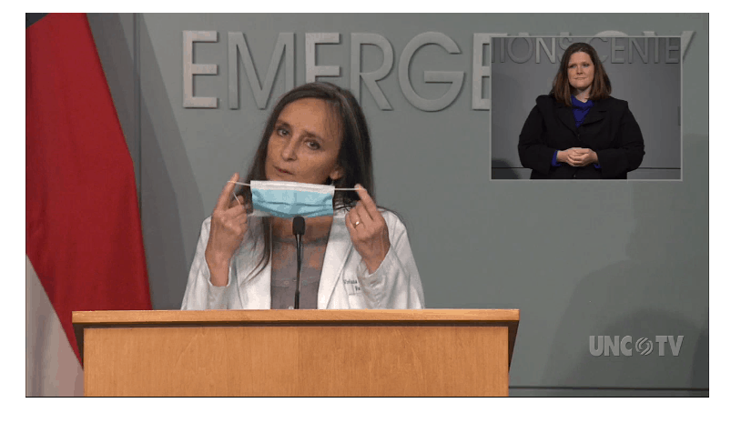 shows a woman in a white coat, holding up a paper surgical mask used to prevent COVID-19 transmission in front of her face