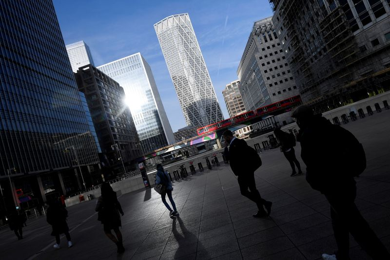 © Reuters. FILE PHOTO: People walk during the morning rush hour in the financial district of Canary Wharf amid the outbreak of the coronavirus disease (COVID-19) in London