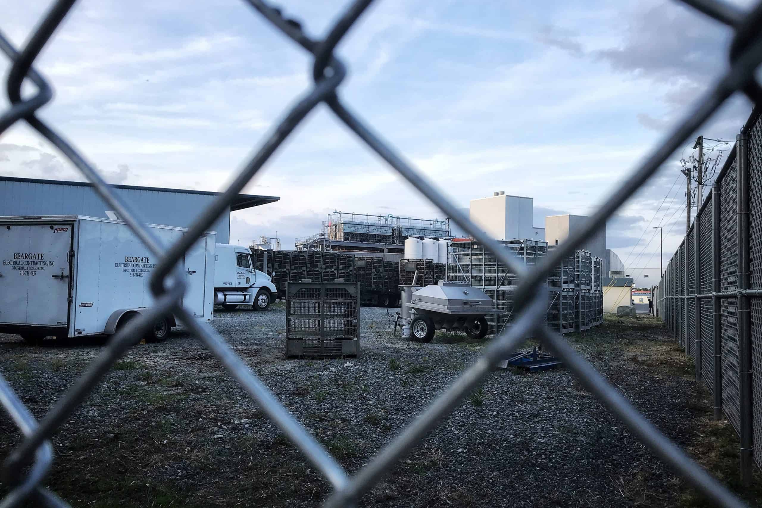 we look through a chain link fence into an industrial complex / poultry plantwhere multiple workers have tested positive for COVID-19