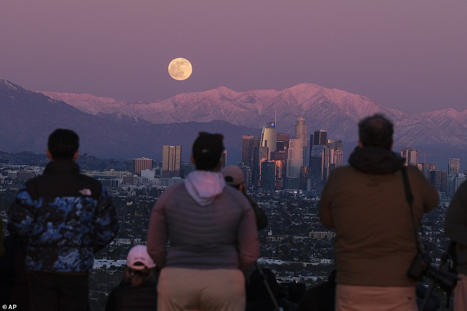 People watch as the full moon rises over snow covered mountains, behind downtown Los Angeles