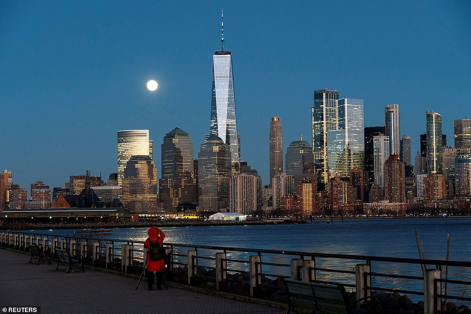 A woman tries to take a picture of the full moon known as Cold Moon as it rises behind One World Trade Center, viewed from Jersey City, New Jersey