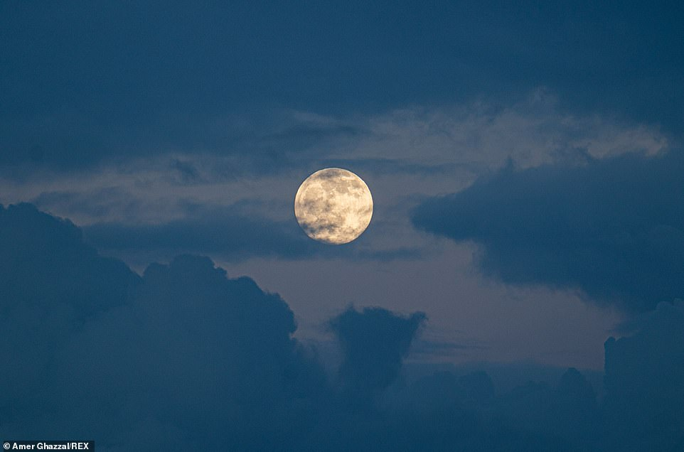 A full moon appears at sunset over the town of Anguillara Sabazia, Lazio in Italy