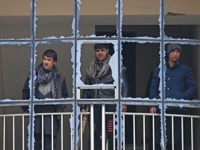 © Reuters. Afghan men look out from a damaged window of their building at the site of a blast in Kabul