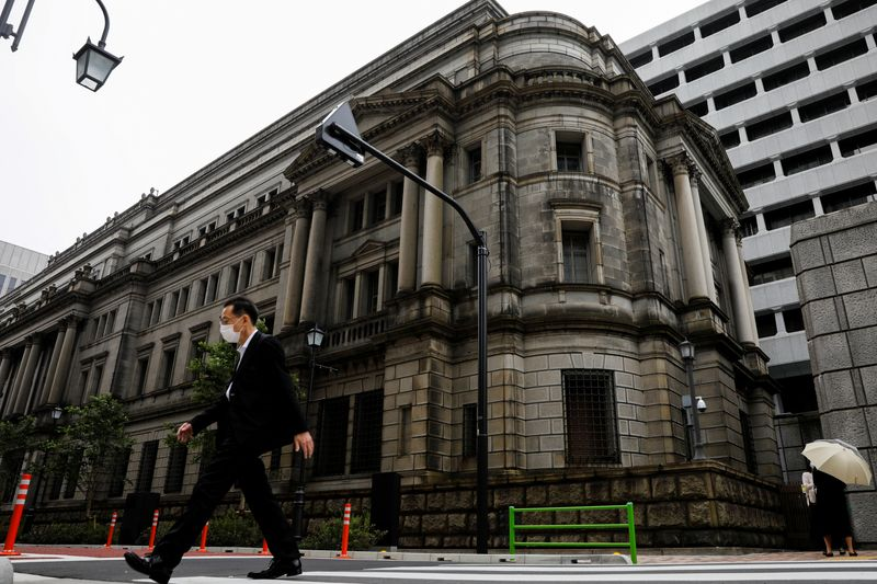 © Reuters. FILE PHOTO: A man wearing a protective mask walks past the headquarters of Bank of Japan amid the coronavirus disease (COVID-19) outbreak in Tokyo