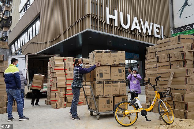 Workers move computers on a street in the Chinese City of Wuhan last week. The communist state looks set to be the only major economy in the world to have grown last year