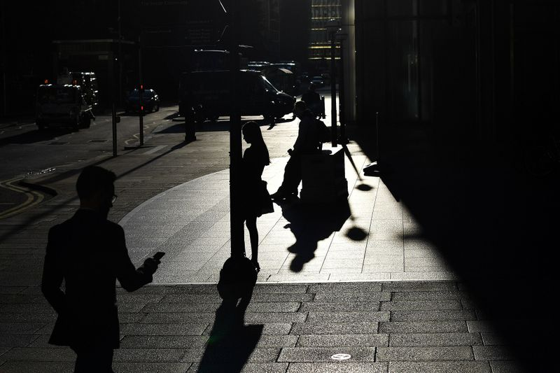 © Reuters. The early morning sun silhouettes commuters as they make their way through Canary Wharf in London