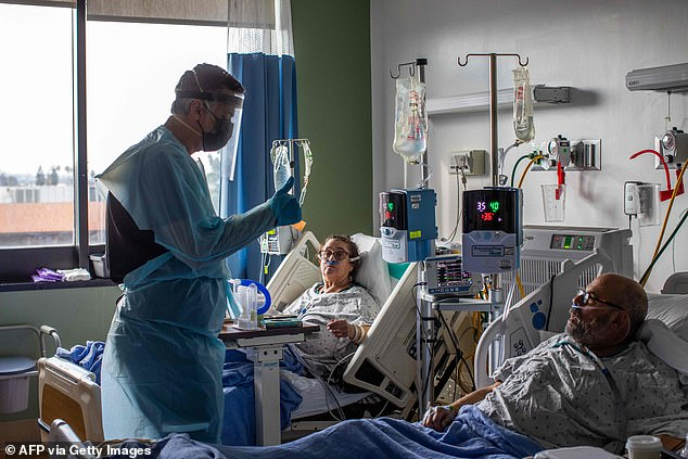 New coronavirus strains may be able to bypass the immune response that COVID-19 survivors have developed and allow for easier reinfection. Pictured:Medical Director of the ICU Dr Thomas Yadegar checks the vital signs of Dr Neil Hecht and his wife Mindy Cross (center) at Providence Cedars-Sinai Tarzana Medical Center in Tarzana, California, January 3
