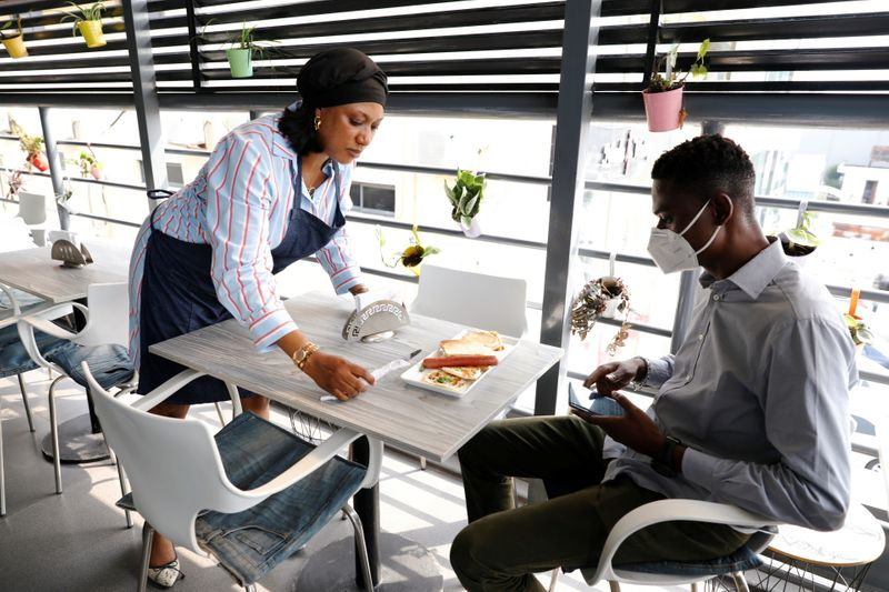 © Reuters. Melanie Igbe, head chef at Cafe de Elyon, attends to a customer at the cafe in Lekki, Lagos