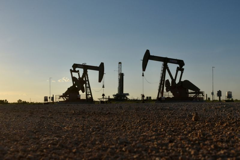 © Reuters. FILE PHOTO: FILE PHOTO: Pump jacks operate in front of a drilling rig in an oil field in Midland