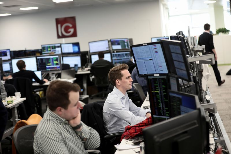 © Reuters. Traders look at financial information on computer screens on the IG Index trading floor