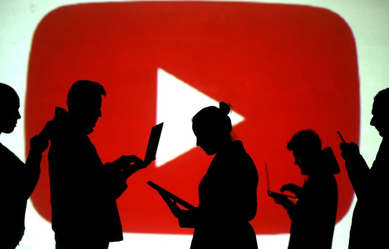 © Reuters. FILE PHOTO: Silhouettes of laptop and mobile device users next to a screen projection of the YouTube logo in this picture illustration