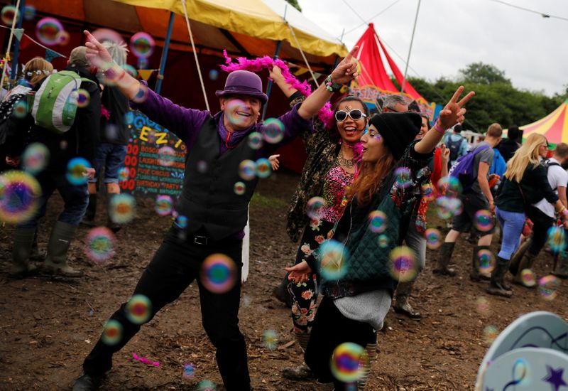 © Reuters. Revellers react while being photographed at Worthy Farm in Somerset during the Glastonbury Festival
