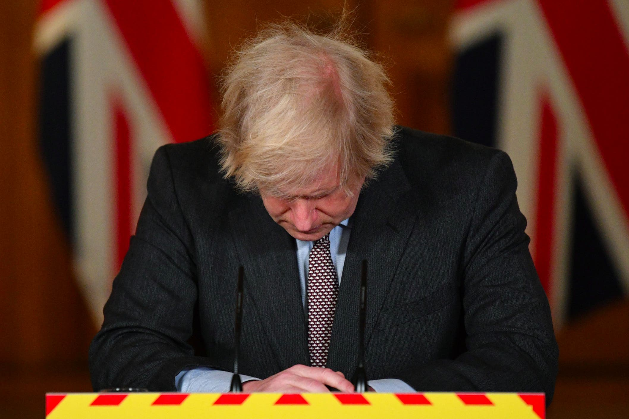 Boris Johnson looks down at the podium during a media briefing after the UK recorded 100,000 coronavirus deaths
