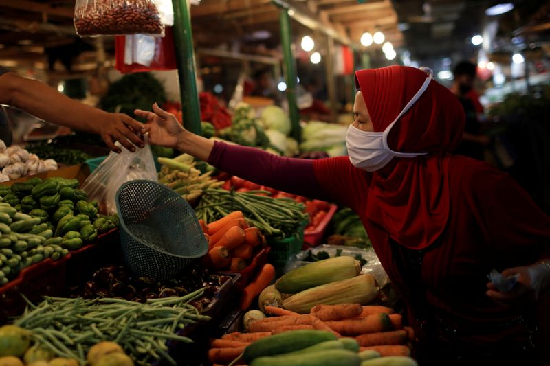 © Reuters. A woman wearing a protective mask shops for vegetables at a traditional market, as the coronavirus disease (COVID-19) outbreak continues, in Jakarta