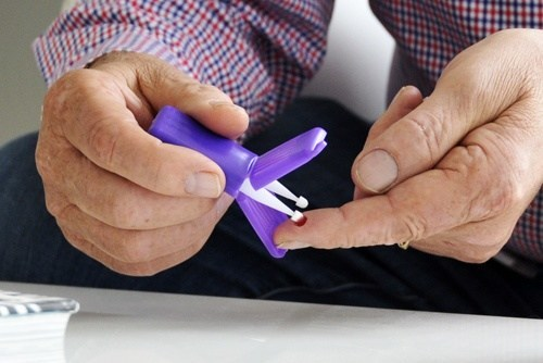 A study participant collects blood at home using a Mitra device with VAMS technology from Neoteryx. (PRNewsfoto/Neoteryx)