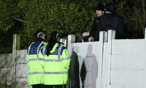 A couple of PCSOs talk to some fans who are watching the game from outside of the ground.