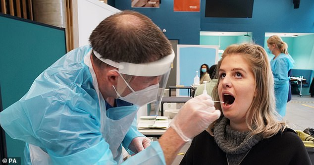 The Department of Health said they have adequate PPE to protect them from the virus. Above is a tester taking a swab from a student in Newcastle