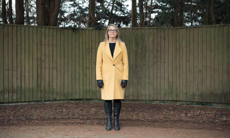 Julie Highfield, a clinical psychologist who works in critical care, in yellow coat, standing against a fence